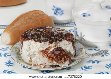 cottage cheese Poured by chocolate with nutlets, a roll on a napkin - stock photo