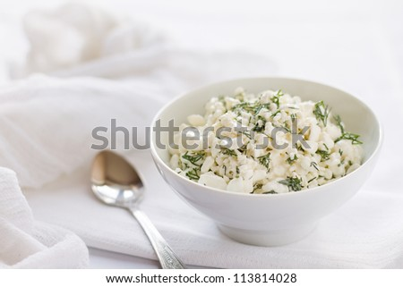 Cottage cheese served with dill on a white tablecloth