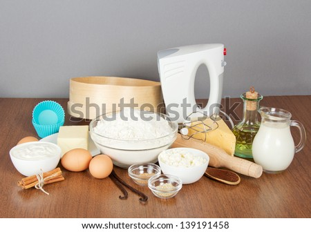 Cottage cheese, sour cream, cheese, butter, mixer and cake pan on a table, on a gray background