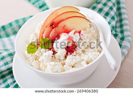 Cottage cheese with apple, berry syrup and sour cream for breakfast close up - stock photo