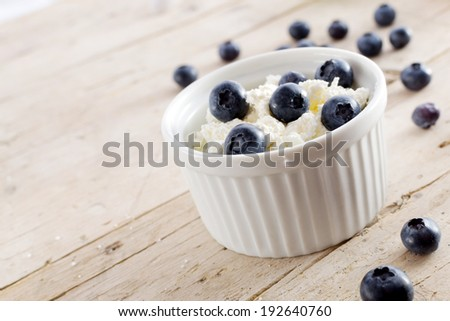 Cottage cheese with blueberries on wood - stock photo