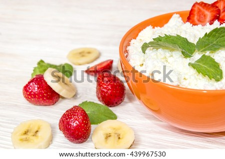 Cottage cheese with strawberry, banana and mint on white wooden table