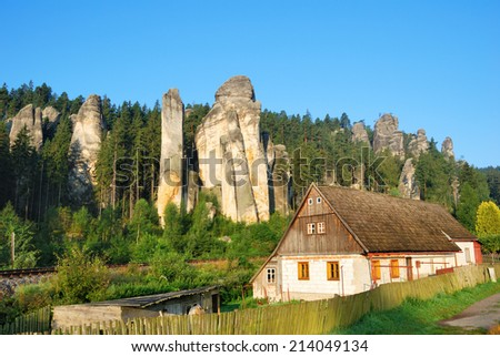 Cottage house with forest and sandstone towers behind - stock photo