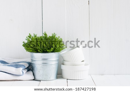 Cottage life, country kitchen decoration: a house plant in a metal pot, kitchen pottery, utensils and napkins on white painted board. Cozy home country life background is. - stock photo