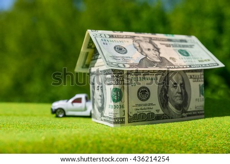 Cottage made of dollar banknotes, housing and car loan.  - stock photo