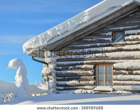 Cottage on snowy mountain on a sunny cold winter day on tourist resort in Lapland Finland. Cottage and spruce trees are covered by heavy snow.  - stock photo