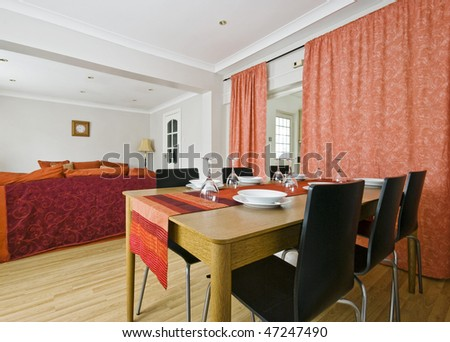 cottage style interior with dining table and living area - stock photo