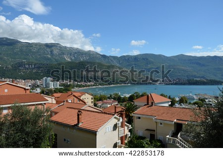 Cottages by the sea on a background of mountains on sunny day