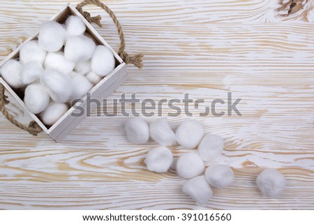 Cotton balls in a box on wooden table - stock photo