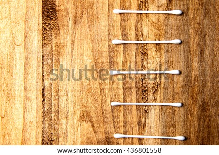 Cotton buds on a wooden background - stock photo
