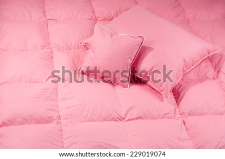 Cotton pink fluffy two pillows on big duvet without cover, eiderdown filled with fluff or feathers. Horizontal orientation, nobody.