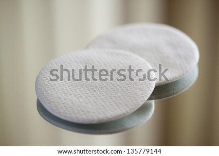 Cotton round cosmetic pads on reflective surface, close-up