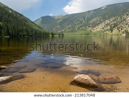 Cottonwood lake in the valley before pass over mountains on clear calm day with the lake stretching off to distance - stock photo