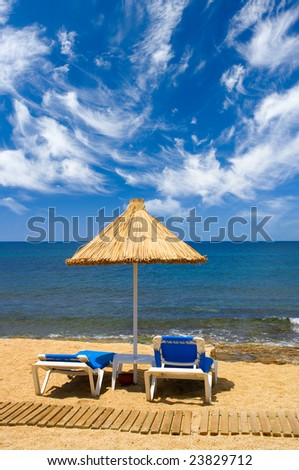 couch and sunshade on the seaside and sky with clouds