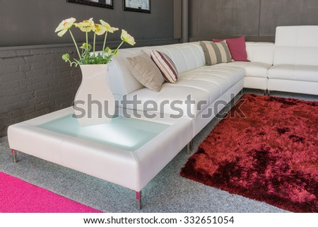 Couch with white upholstery and two pillows - stock photo