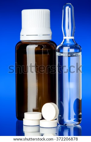 Cough syrup with an ampoule for a vaccine, glass bottle with round tablets on glass with a blue background, nobody. - stock photo