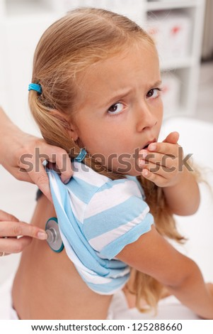 Coughing little girl at the doctors being checked with stethoscope - stock photo
