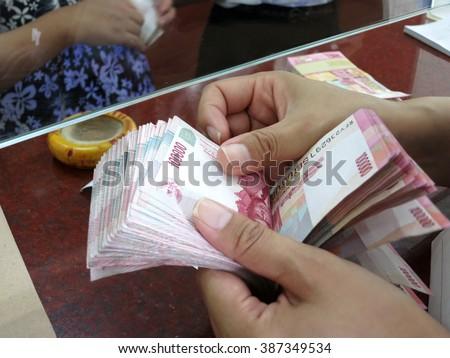 Count Indonesian rupiah money Rp.100,000 with hand in money changer, Kuta, Bali - stock photo