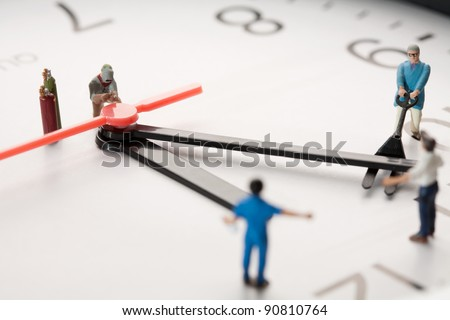 Countdown To Midnight And New Year. A team of miniature toy figurines tries to push the minute hand to midnight, closeup on a portion of a clock face.