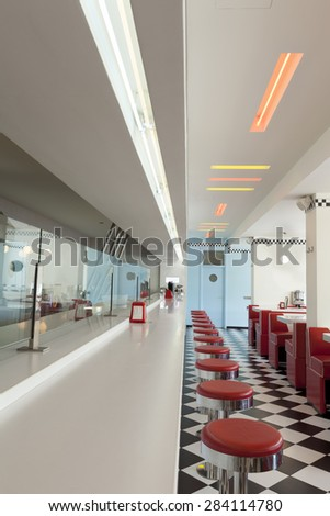 counter and red bar stools in american diner restaurant - stock photo