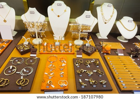 counter with golden jewelry in store window - stock photo