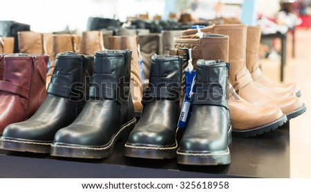 Counter with wintry male shoes at  shop - stock photo