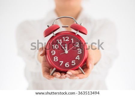 Counting hours expecting child birth. Motherhood concept. Pregnant woman holding alarm clock, studio shot. - stock photo
