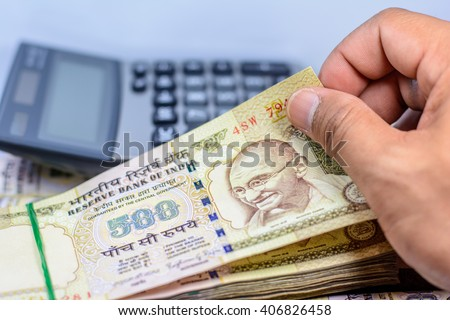 Counting Indian rupee currency,money with blurry calculator on background,Focus on eye of Gandhi - stock photo