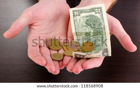 Counting money in hand on wooden table background - stock photo