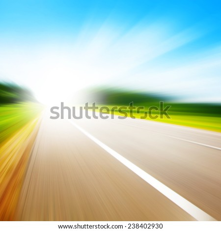 Country asphalt road in motion blur and sunlight. - stock photo