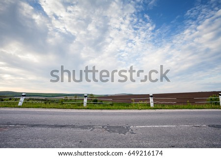 Country asphalt road side view with field on background, evening landscape