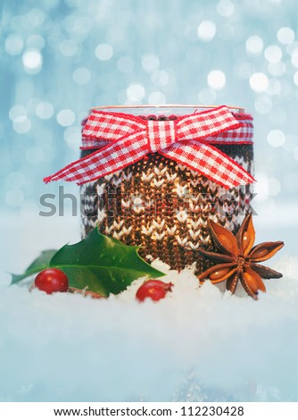 Country Christmas decoration still life with holly and spice in snow against a sparkling bokeh of party lights - stock photo