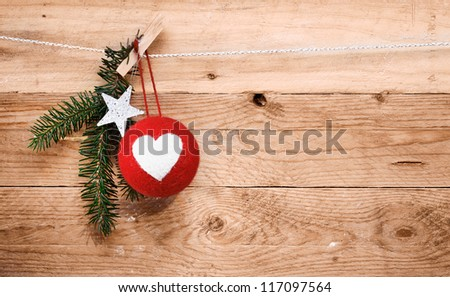 Country Christmas decorations with a red handcrafted fabric bauble decorated with a heart, a star and sprig of pine hanging on a line over natural wooden boards with woodgrain texture and copyspace - stock photo
