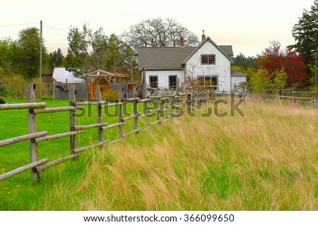 country comfort , farm house in the rural outskirts . wooden home and fence,  refuge away from the city - stock photo