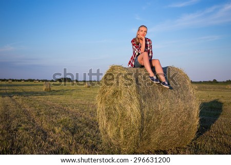 country concept - young woman sitting on haystack over blue sky - stock photo