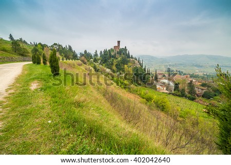 country dirt road bordered by cypress trees next to the clock tower of the village of Brisighella in Italy