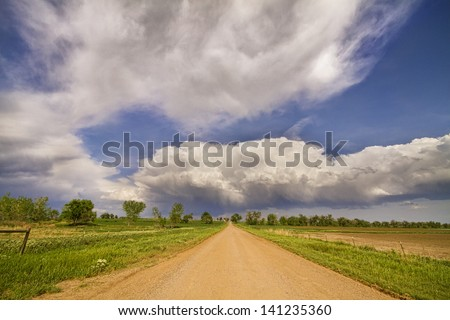 Country dirt road into the horizon of stormy Colorado skies above, Boulder County.   - stock photo