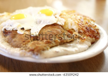 Country fried steak with gravy along with eggs sunnyside up and hash ...