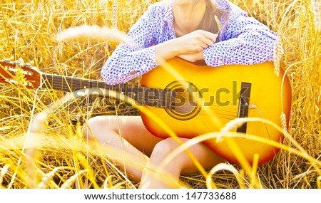 Country  girl sitting with acoustic guitar at reap wheat field Copy space for inscription - stock photo
