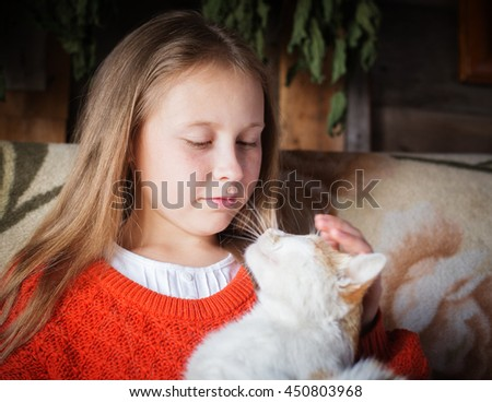 Country girl stroking a cat.