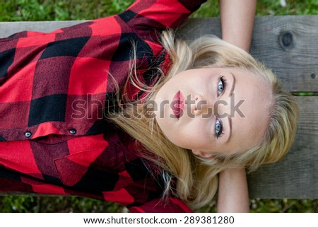country girl thinking seriously about the future on a bench in the nature - stock photo