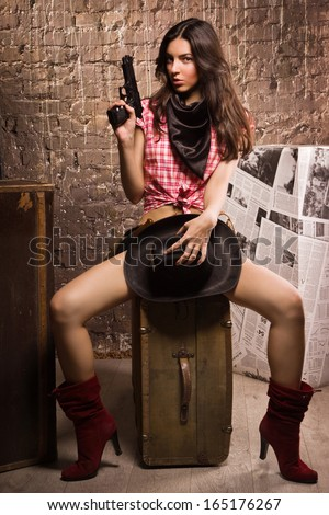 Country girl with gun sitting on a vintage suitcase