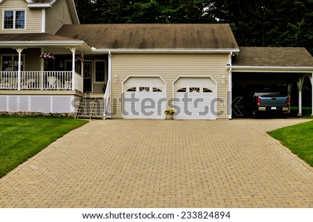 Country home with a double garage and a truck under carport - stock photo