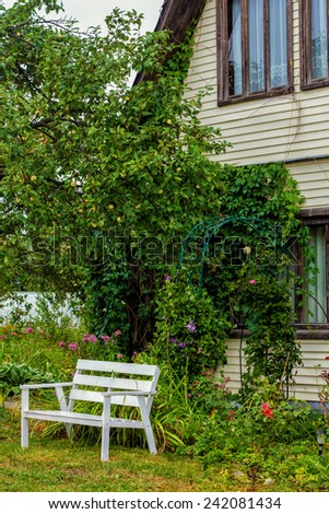 Country House entwined with ivy next to the garden and a white garden bench