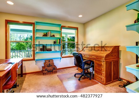 Country house home office interior with blue shelves, two desks and decorated with wicker chest set. Northwest, USA