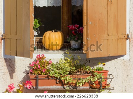 Country House Window with a Pumpkin and Flowerpots on the Windowsill - stock photo