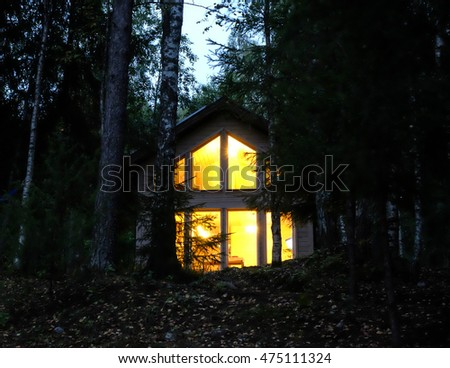 country house with burning large panoramic Windows in the night forest