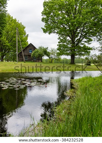 country house with pond and oak trees in green summertime