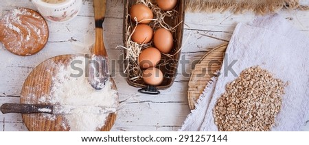 Country kitchen still life for baking ingredients for cooking from above. Oat flakes flour and  flour in the wooden board with wicker basket of eggs over on white wooden kitchen table.
