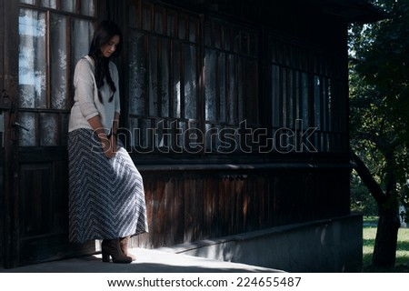 country lady standing near the house  in the afternoon